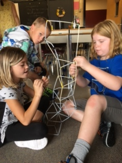 Two female students work with pipe cleaners to build a tower