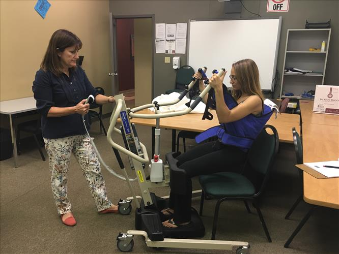 A student and instructor work to demonstrate safe use of a mobility assistance device
