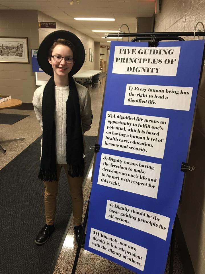 A student poses with a poster indicating the principles of dignity