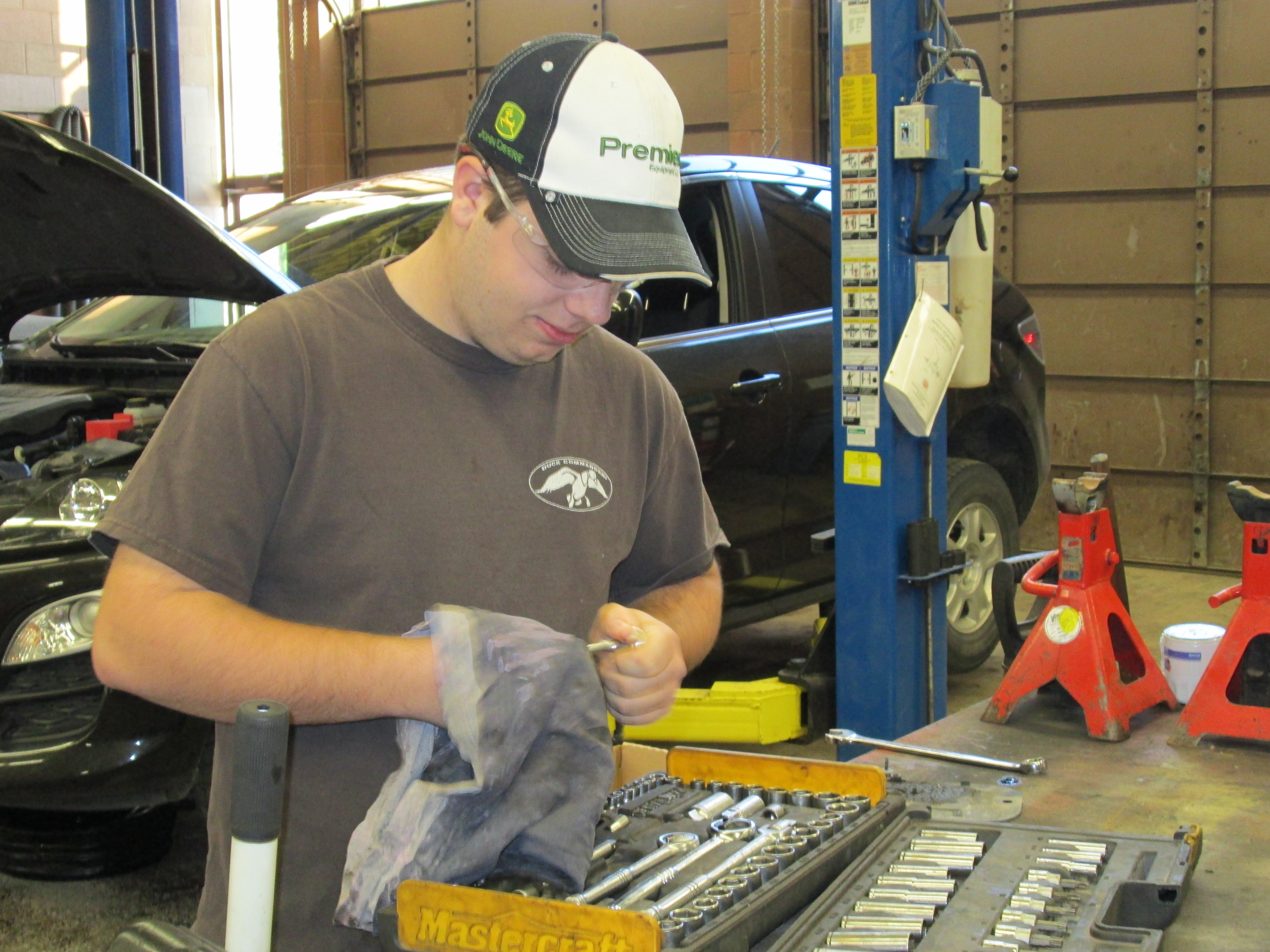 A student works in an automotive mechanic shop