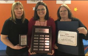Teachers smile while holding a plaque
