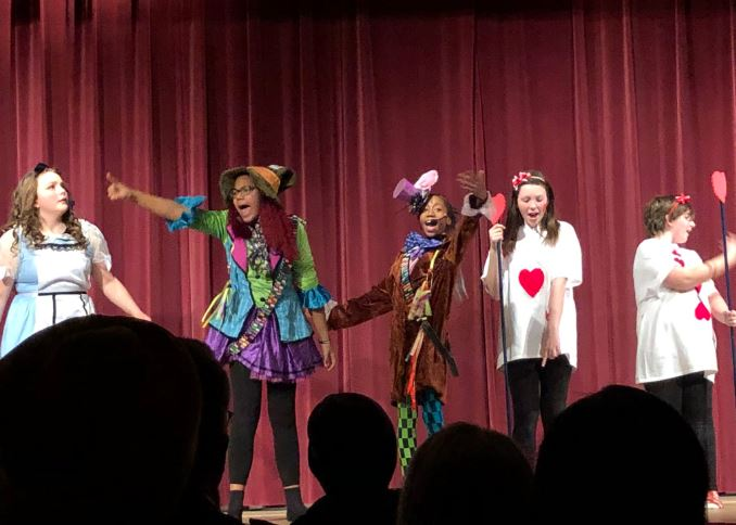 Students perform Alice in Wonderland in costume
