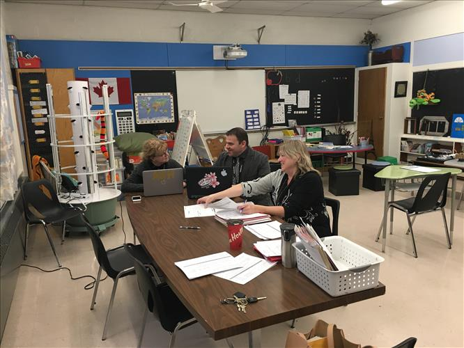 Three staff members sit at a table in a classroom