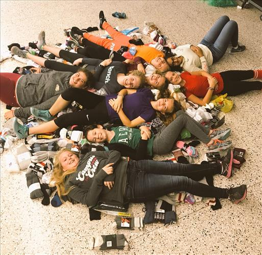 A group of students reclines in a hallway among hundreds of pairs of socks