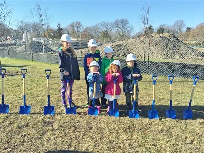 A group of students wears hardhats and holds shovels during groundbreaking celebrations