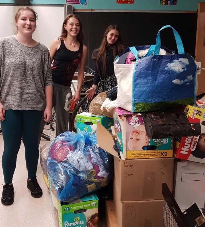 Three female students sort through donations