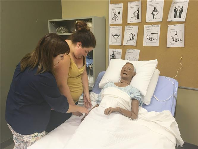 A student and instructor work with a patient simulator dummy