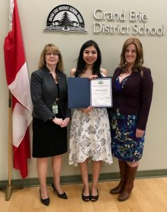 A young woman holds a certificate with two smiling women on either side of her