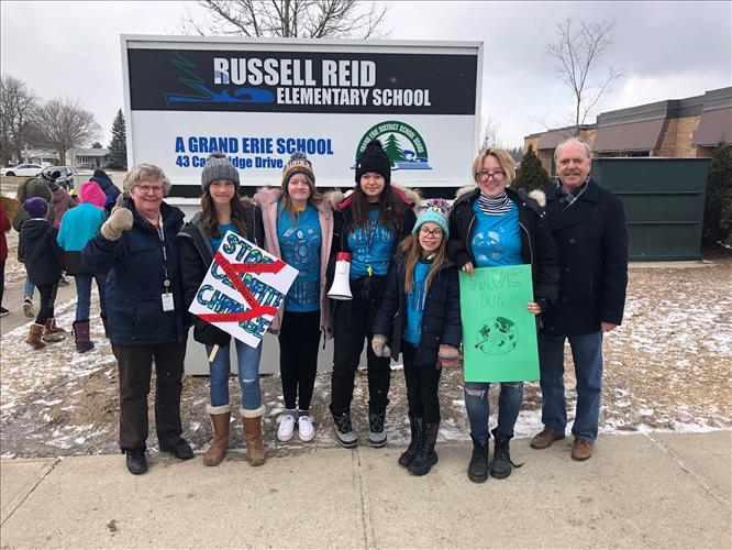 Students stand with a Trustee and a City Counselor during a climate change rally