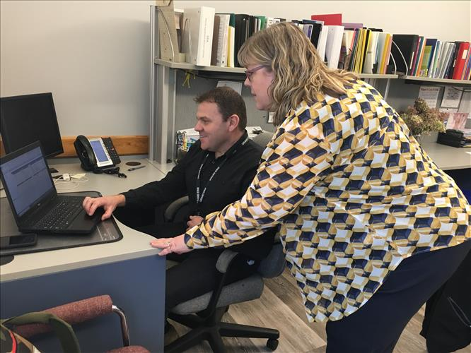 Two staff members collaborate at a computer screen