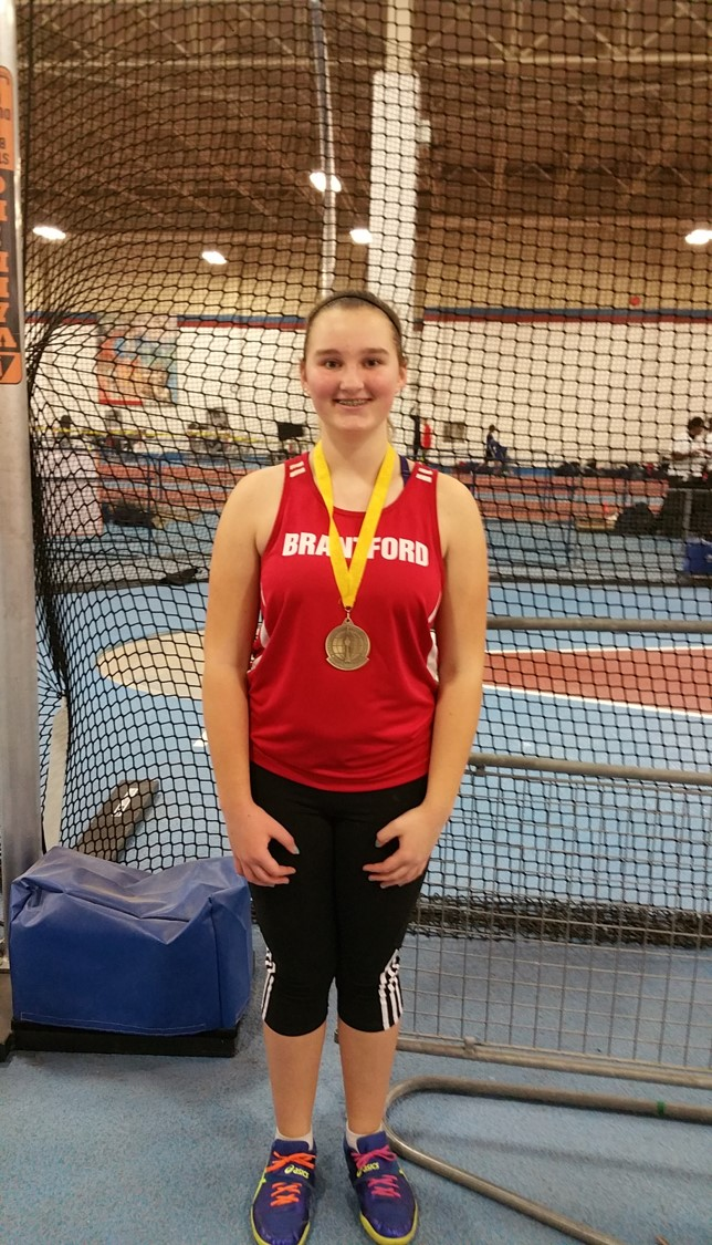 Female student in athletic uniform stands with medal around her neck