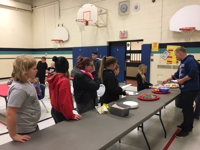 Students are served a hot breakfast by teachers