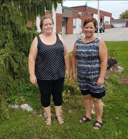 Two smiling Educational Assistants stand outside of school