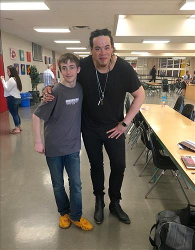A young male student poses with a musician