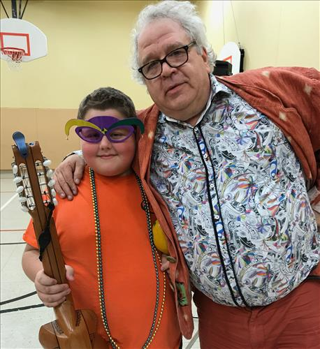 A sharply dressed musician poses with a young student holding an instrument and wearing Mardi Gras beads