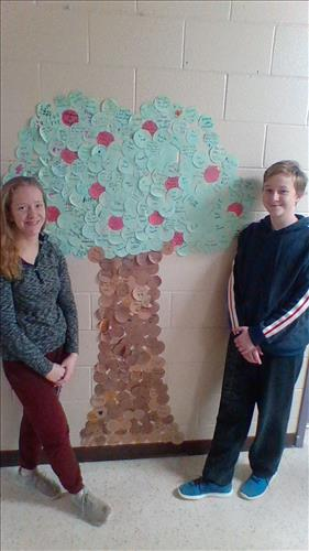 Two students stand on either side of a paper tree display with messages written on the leaves