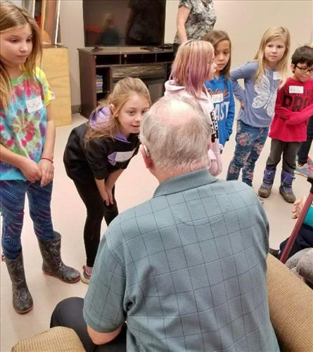 A group of elementary students converses with older adults at a retirement home