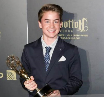 A smiling young man holds an Emmy Award