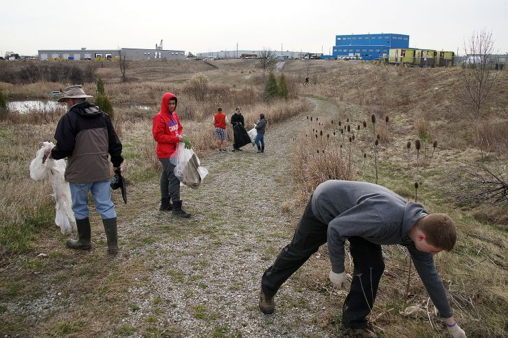 Students pick up trash in a grassy field