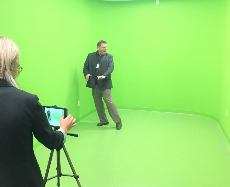 A man dances in front of a green screen