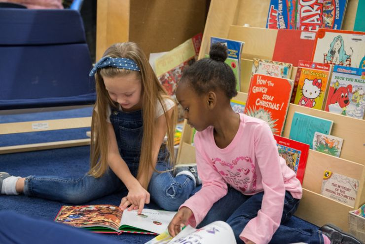 Two primary-grade students sit on a carpet reading books