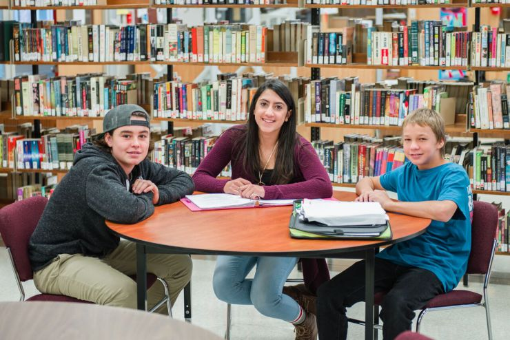 Three students sit at a table in a library with notebooks