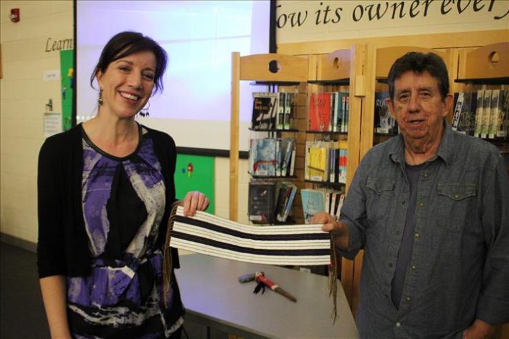 Two people hold a wampum belt