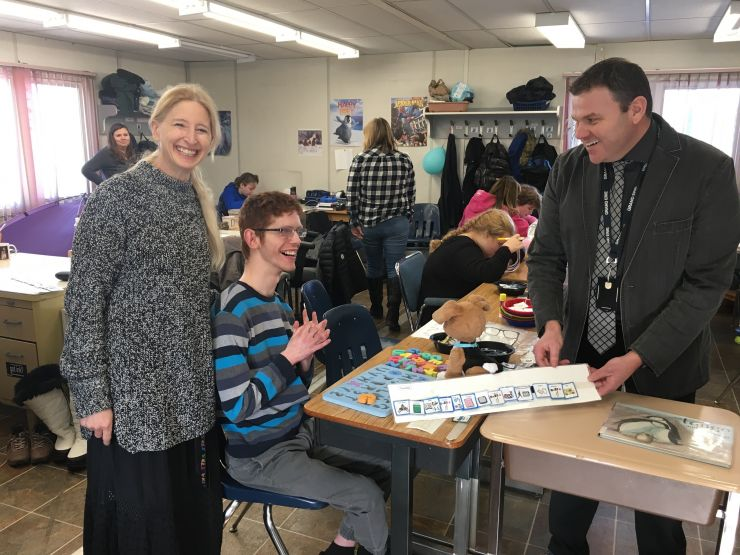 Two staff members work in a classroom with students with autism