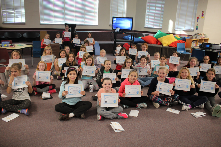 A group of girls seated on floor holds certificates