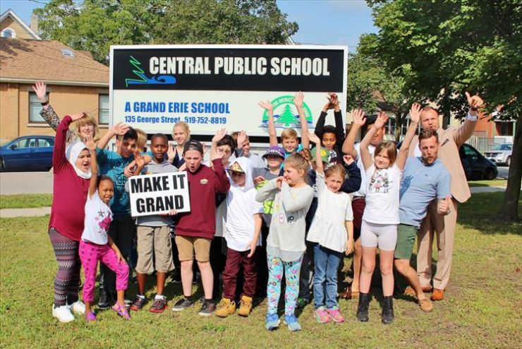 A group of students and staff poses in front of Central Public School sign
