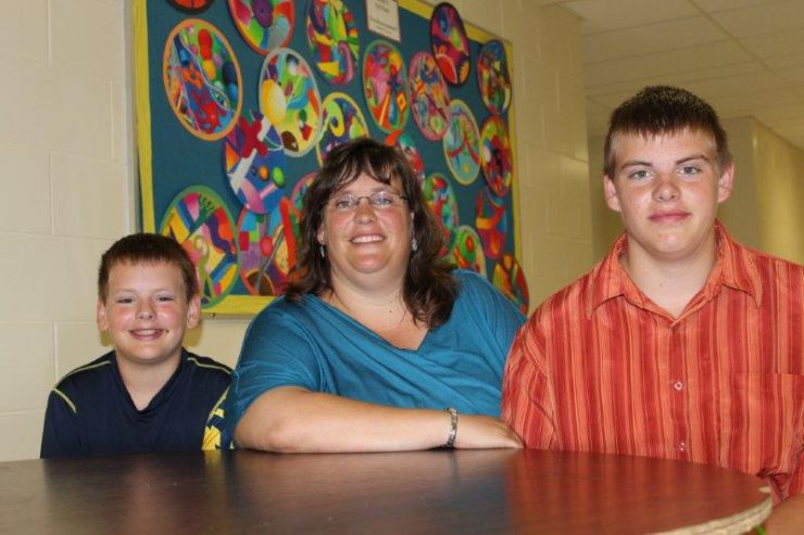 A teacher and two students smile