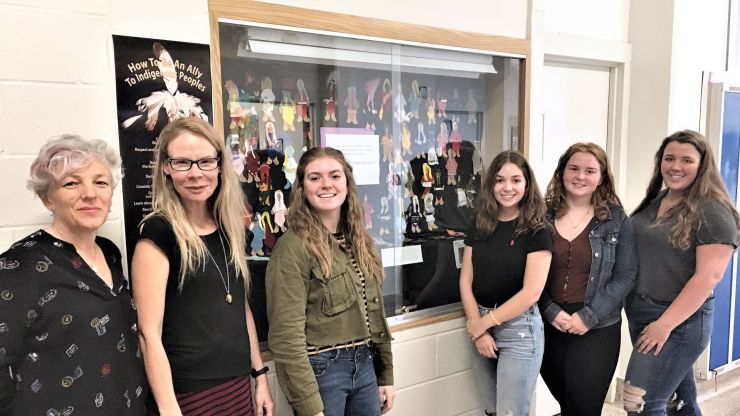 Librarian Amanda Van Schyndel, Teacher Amanda Vincent, and students in the World Cultures class pose in front of the Faceless Dolls display