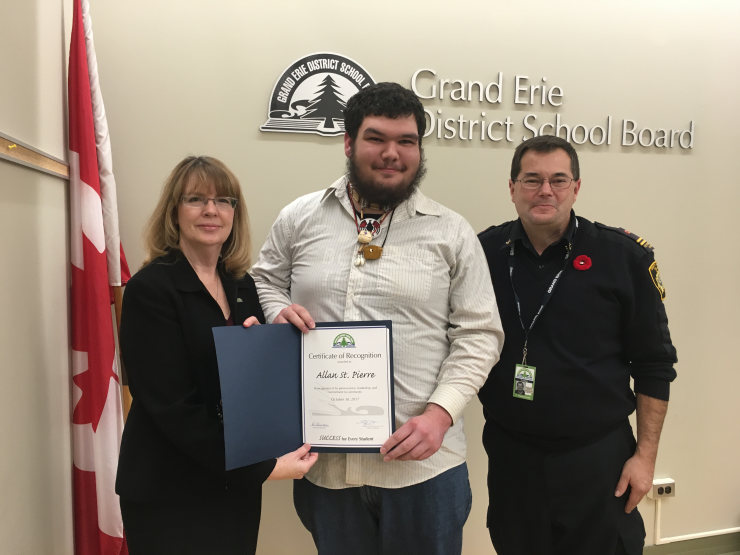A smiling young man poses with a certificate, presented by two adults