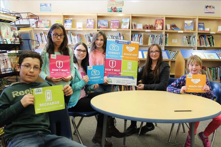 A group of students poses with Be Well posters