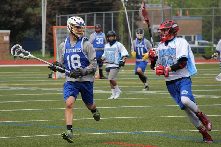 Secondary students run across a field wearing helmets and carrying sticks during a game of lacrosse