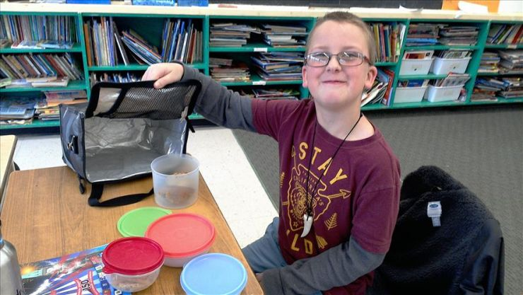 A boy shows off his litterless lunch