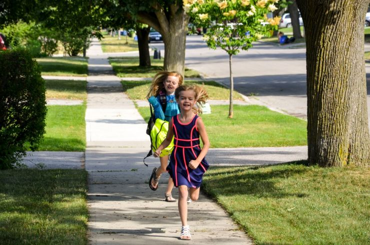 Two smiling girls with backpacks on run down the sidewalk.