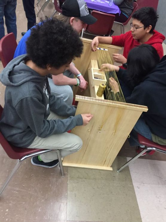 Students use a loom to bead
