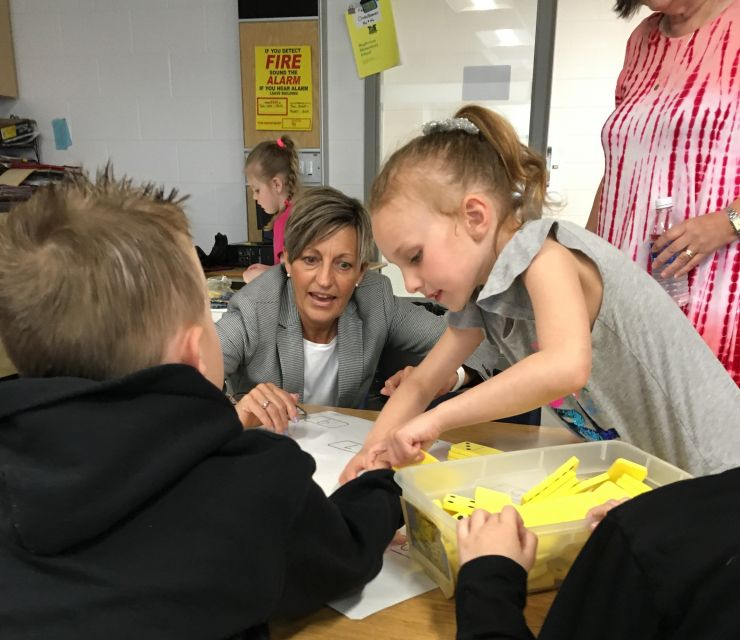A woman wearing a suit plays with Kindergarten students