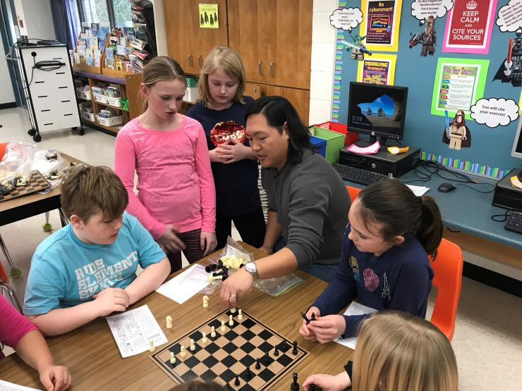 Students watch and listen as community volunteer leads chess lesson