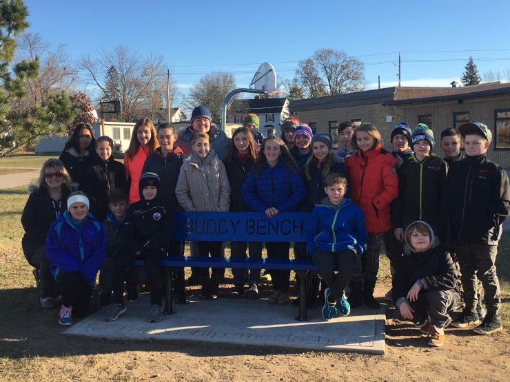 Students pose in front of the school yard's new Buddy Bench