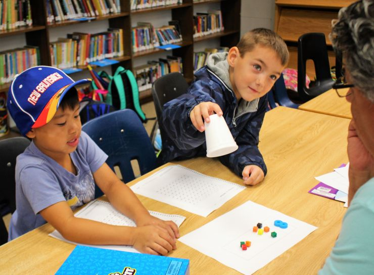 students sitting at a table lifting up cup to reveal math manipulatives