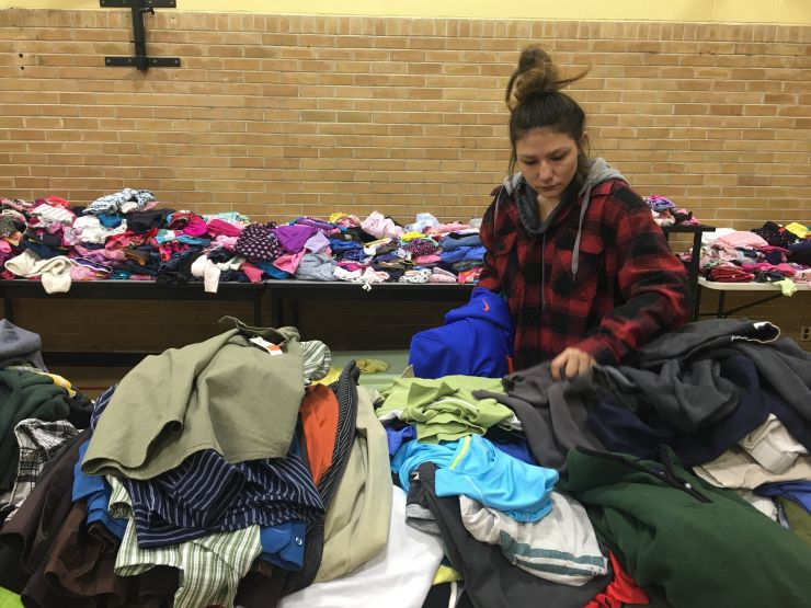 A young woman sorts through clothing donations