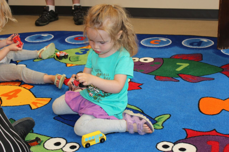 A young girl plays on a play mat