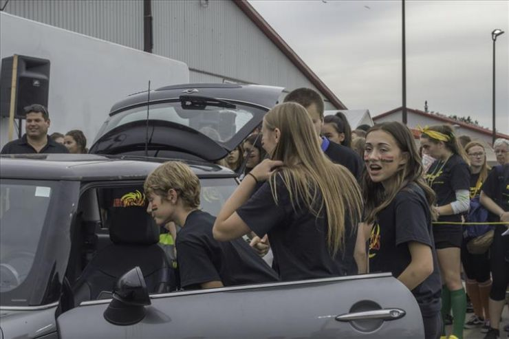 A group of Grade 9 students peers into a small car