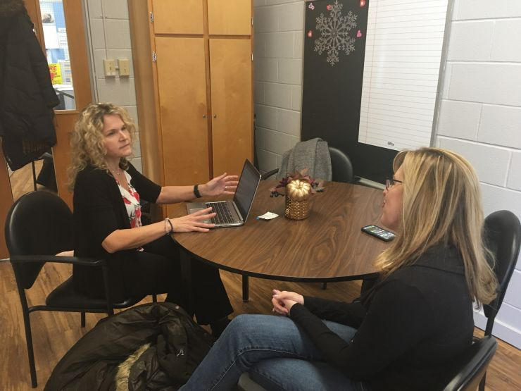 A specialist sits at a laptop while consulting with a principal