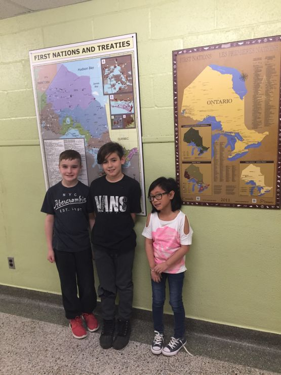 Three students stand under a poster of a map depicting First Nations treaties