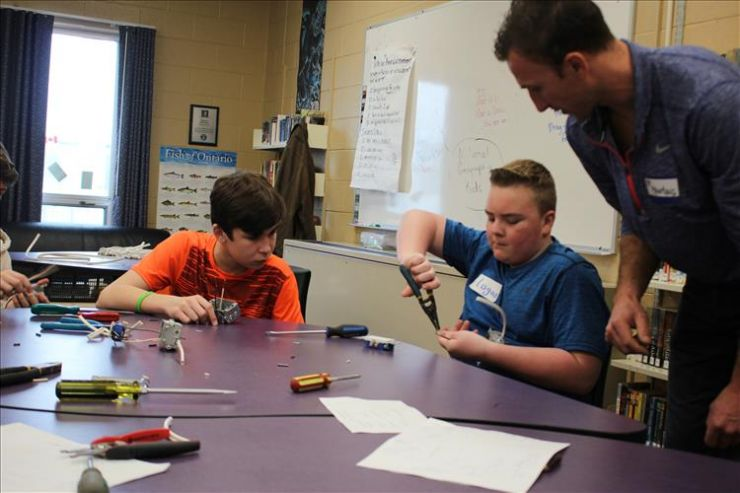 Students learn to strip a wire with the help of electrician looking on