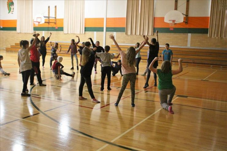 Students participate in a dance class in a school gymnasium