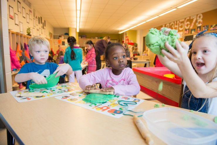 Three children are seated at a table in a classroom where they play with molding clay